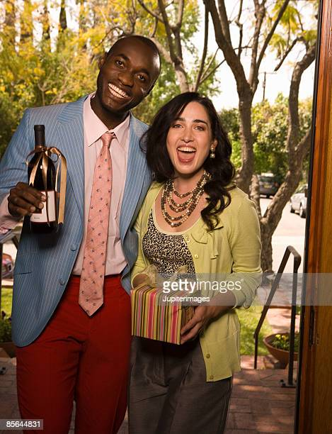 Couple holding gift and bottle of wine