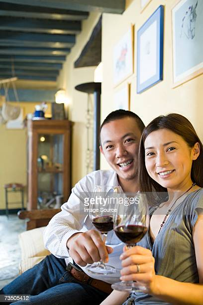 Couple holding glasses of red wine