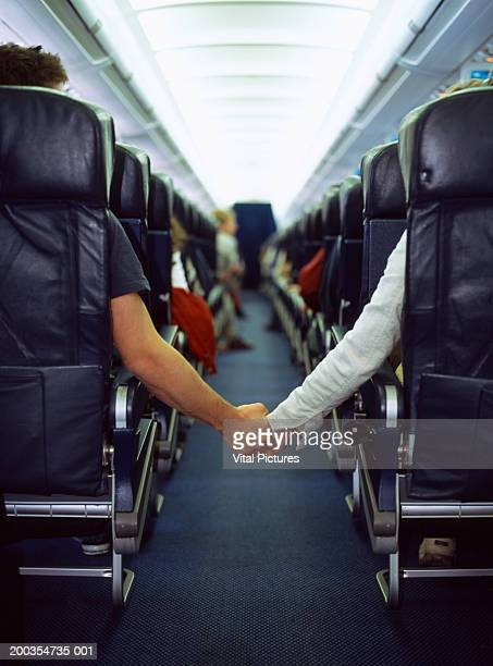 Couple holding hands across aisle of passenger aeroplane, rear view