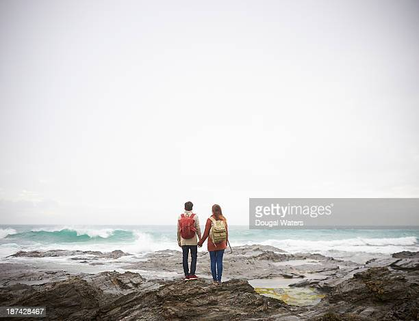 Couple holding hands and looking out to sea.