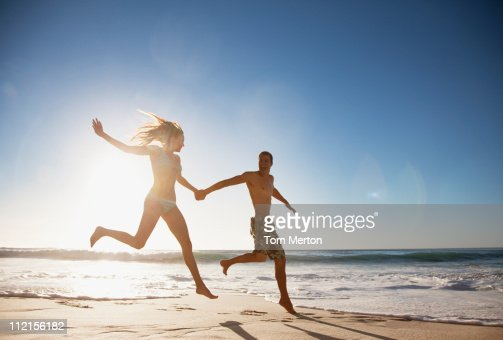 Couple holding hands and running on beach : Stock Photo