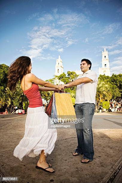 Couple holding hands and spinning outdoors