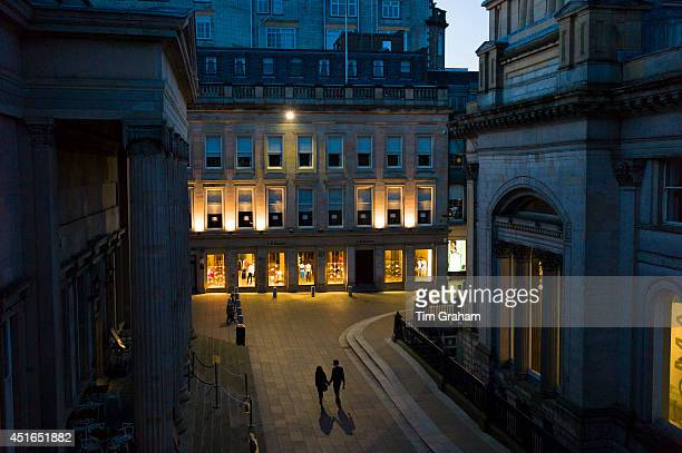 Couple holding hands and taking a nighttime stroll in Royal Exchange Square in the City Centre Glasgow Scotland