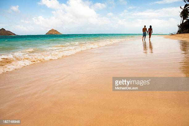A couple holding hands and waking down a beach