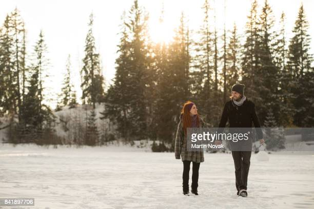 Couple holding hands and walking in winter park