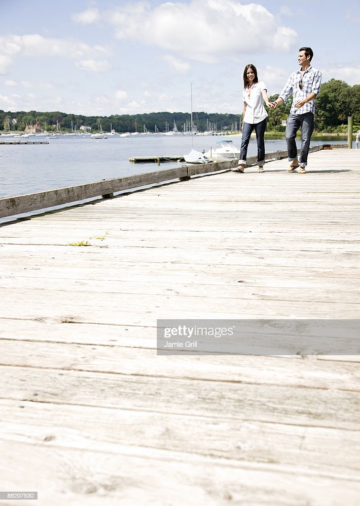 Couple holding hands and walking on dock