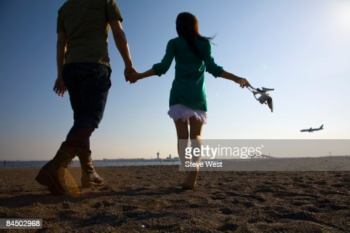Couple holding hands and walking on empty beach : Stock Photo