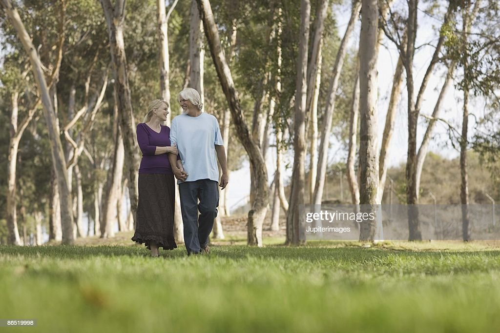 Couple holding hands and walking outdoors : Stock Photo