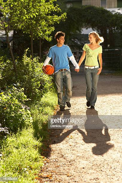 A couple holding hands and walking.