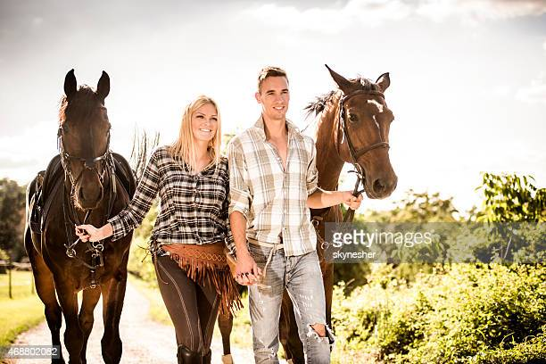 Couple holding hands and walking their horses.