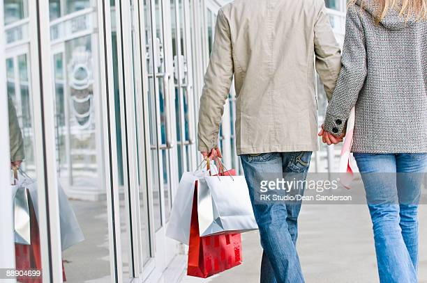 Couple holding hands and walking while shopping.