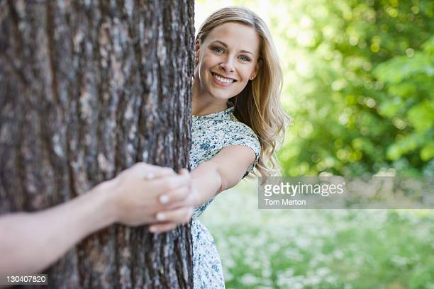 Couple holding hands around tree