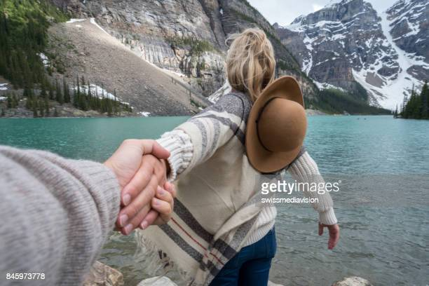 Couple holding hands at mountain lake