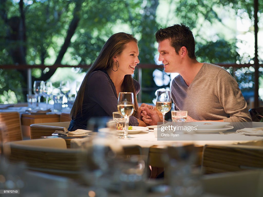 Couple holding hands at restaurant table : Stock Photo