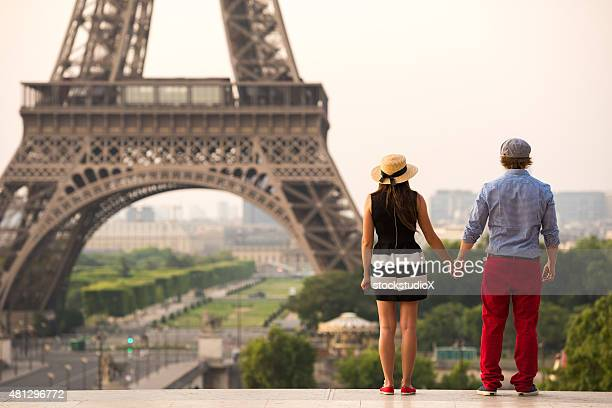 Couple holding hands at the Eiffel Tower in Paris