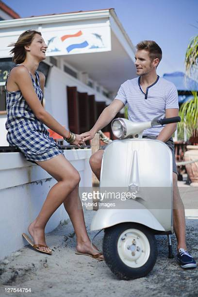 Couple holding hands by scooter