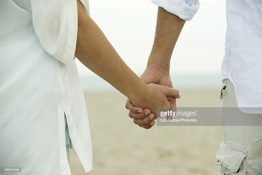 Couple holding hands, cropped