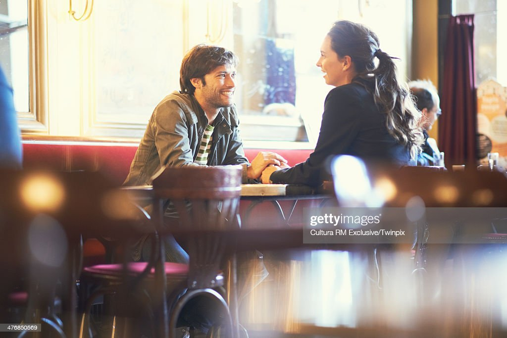 Couple holding hands in cafe bar : Stock-Foto