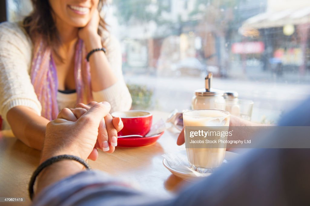 Couple holding hands in cafe : Stock Photo