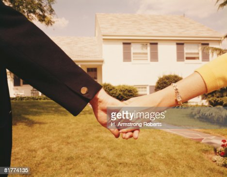 Couple holding hands in front of house. (Photo by H. Armstrong Roberts/Retrofile/Getty Images) : Stock Photo