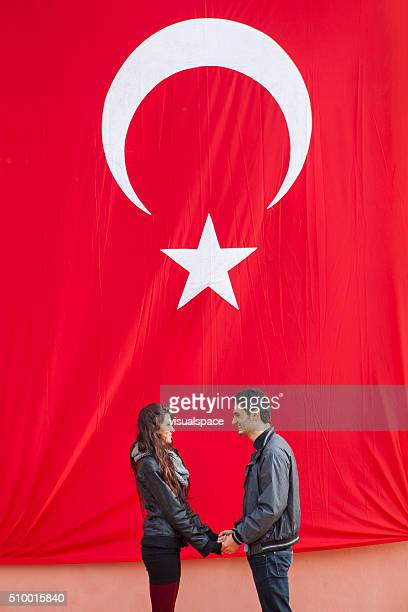 Couple Holding Hands In Front Of The Turkish Flag