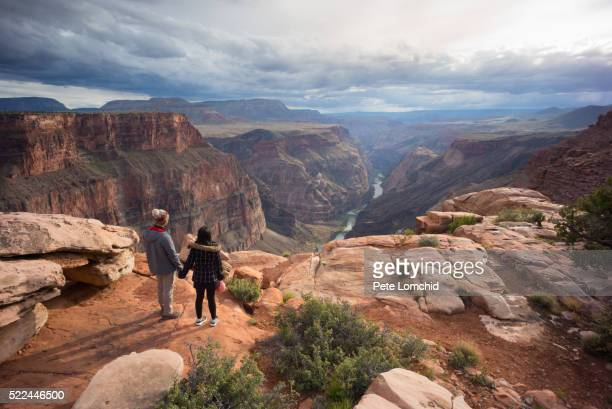 couple holding hands in grand canyon