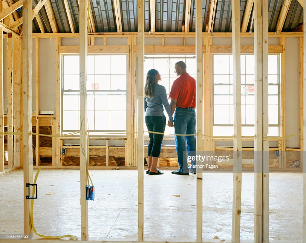 Couple holding hands in home under construction, rear view : Stock Photo