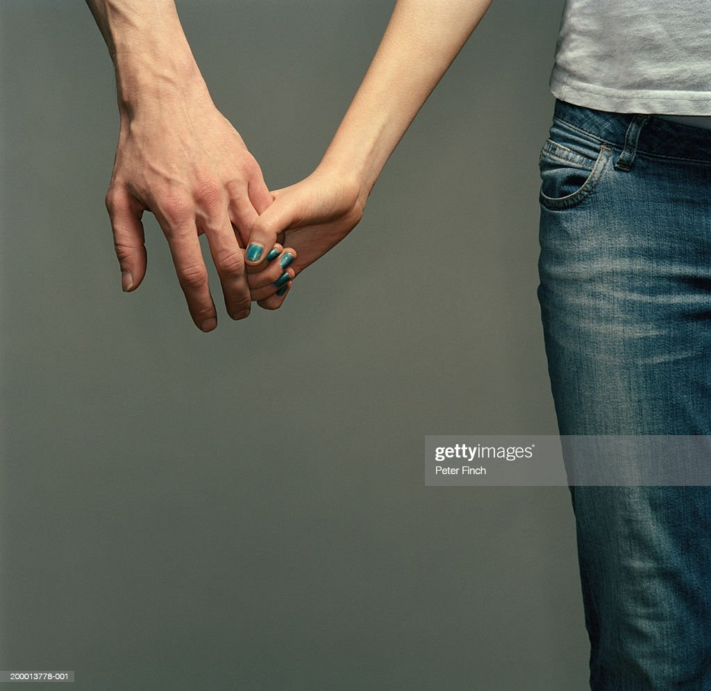 Couple holding hands, mid section : Stock Photo