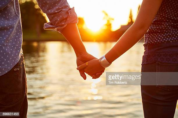 Couple holding hands next to river.