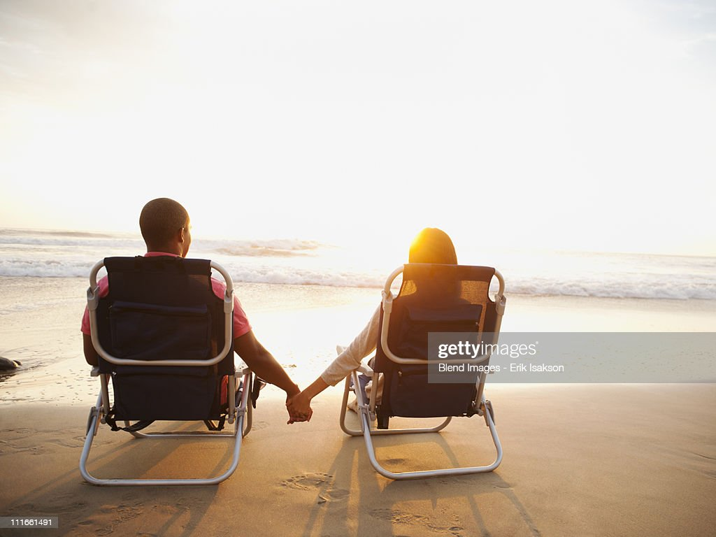 Couple holding hands on beach at sunset : Stock Photo
