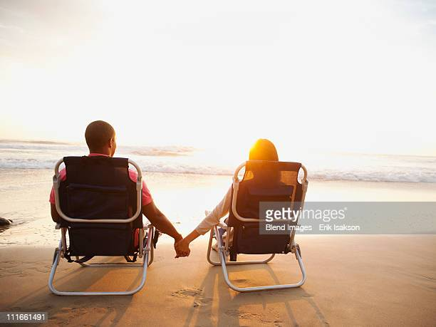 Couple holding hands on beach at sunset