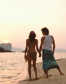 Couple holding hands on beach, sunset, rear view