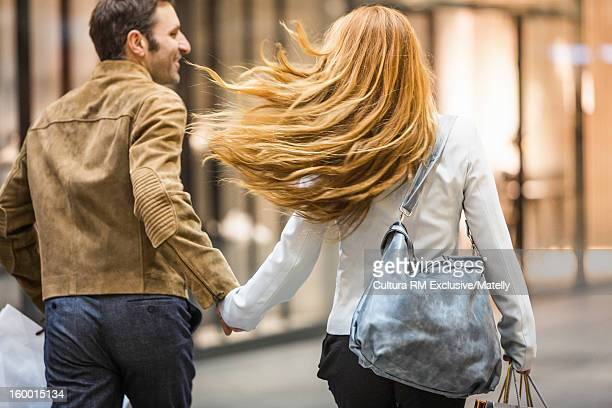 Couple holding hands on city street