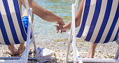 Low section of couple holding hands while relaxing on deck chairs at beach. Male and female tourists are visiting Vis Island during vacation. They are on shore at island.