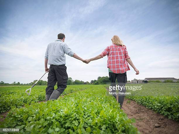 Couple holding hands on farm
