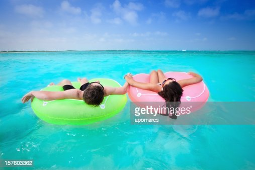 Couple holding hands on floating tubes