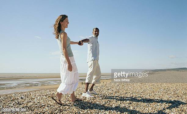 Couple holding hands on pebble beach, laughing