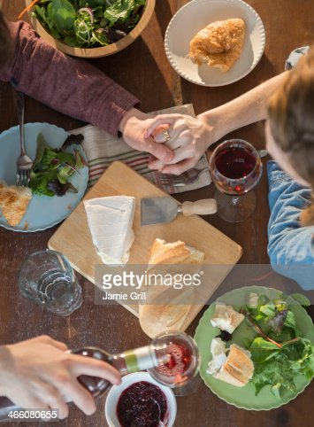 Couple holding hands over dinner table : Stock Photo