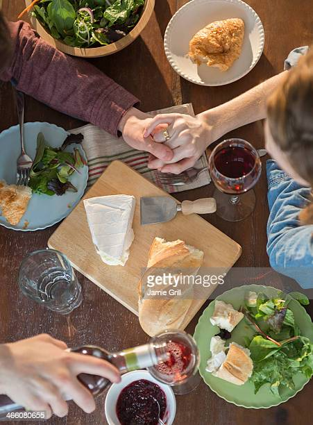 Couple holding hands over dinner table
