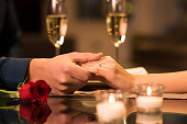 Closeup of couple hands on restaurant table with two glasses of champagne in background. Romantic couple holding each other's hand at dinner in a luxury restaurant. Marriage proposal and engagement co
