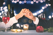 Couple holding hands during romantic dinner.