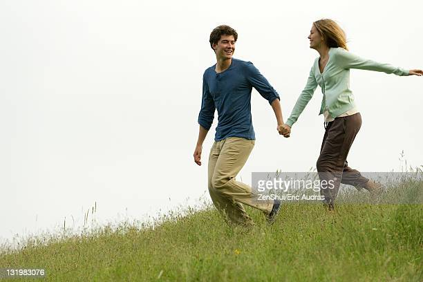 Couple holding hands running on meadow