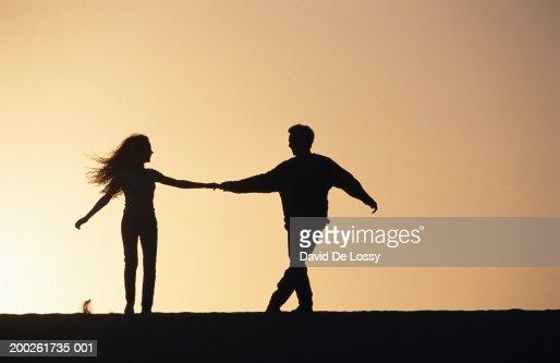 couple holding hands silhouette foto de stock