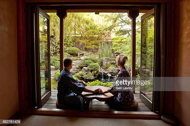 Couple holding hands sitting by a zen garden