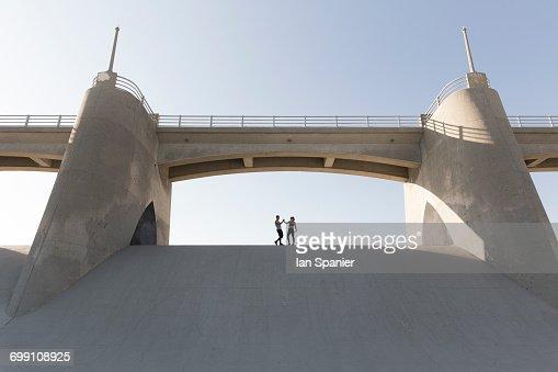 'Couple holding hands under bridge, Van Nuys, California, USA'