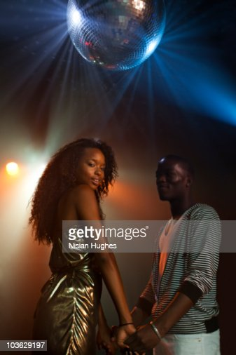 couple holding hands under disco ball : Stock Photo