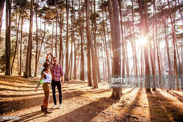 Couple holding hands under trees in sunny forest
