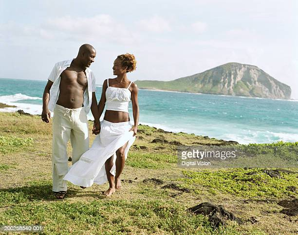 Couple holding hands, walking by ocean