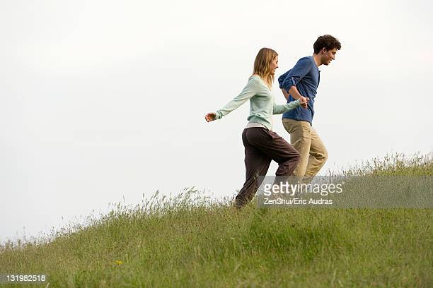 Couple holding hands walking on meadow