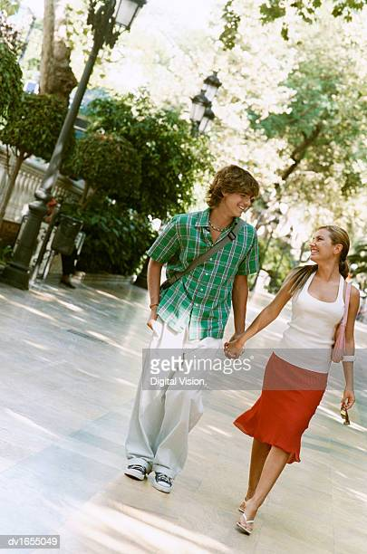 Couple Holding Hands Walking Through a Park